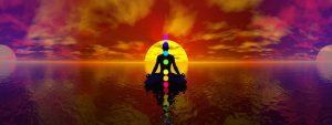 chakras image set in front of a red and purple sunset